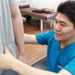 立った状態での腰部の触診を行う坂田大輔