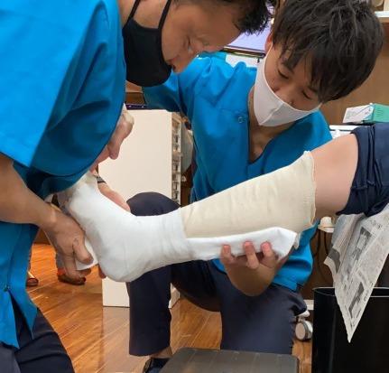 アキレス腱断裂のシーネを包帯固定している様子